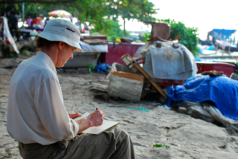 A tourist making sketches as the Sun goes down