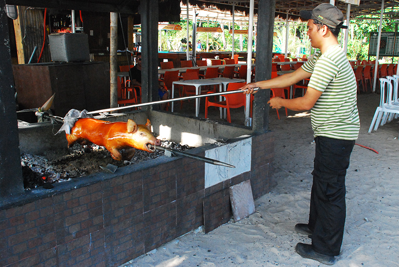 Sights along the White beach - Getting pork ready for dinner